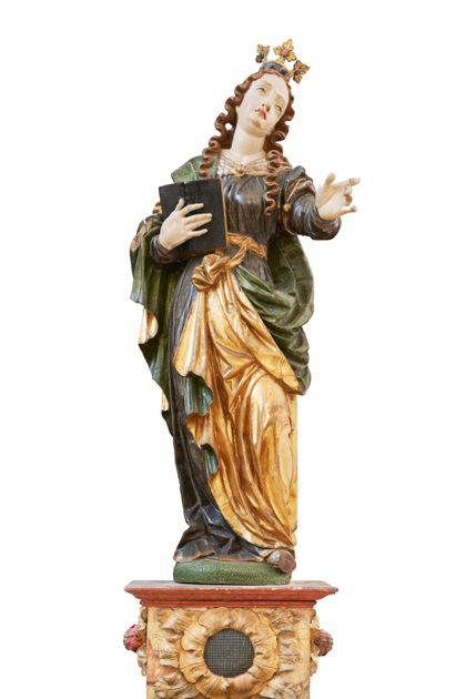 Auf einem Sockel stehende weibliche Heilige, die mit der Linken einen Zeigegestus ausführt und in der Rechten ein Buch hält.