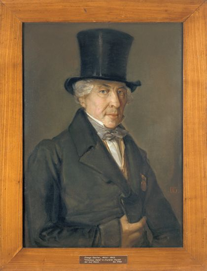 Portrait eines grauhaarigen Herren mit Fliege und gelber Weste, in schwarzem Rock mit Orden und mit schwarzem Zylinder. Hölzern gerahmt.