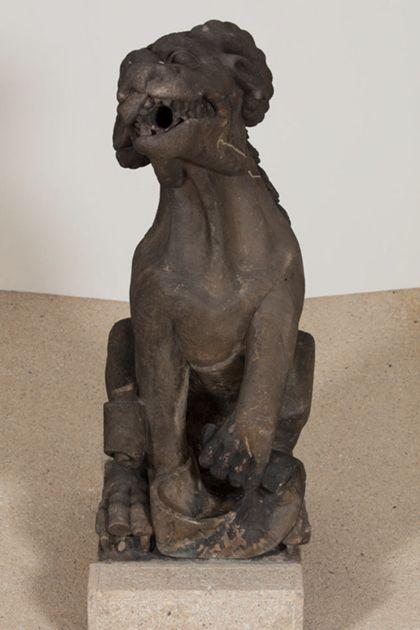 Sandsteinfigur eines hundeartigen Tieres mit Bockshörnern als Wasserspeier, Ansicht von unten.