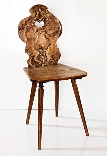 Hölzerner Stuhl, in die Lehne geschnitzt sind Fuchs und Hase, die sich gute Nacht sagen