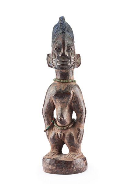 Mänliche Ibeji Figur mit helmartiger Frisur. Am Hals, an der Hüfte und am rechten Arm trägt die Figur je eine Perlenkette.