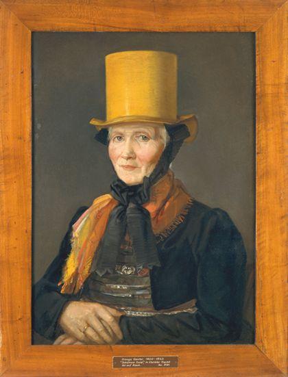 Portrait einer älteren Dame in Tracht, mit gelbem Zylinder. Hölzern gerahmt.