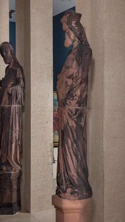 Stark beschädigte, überlebensgroße Sandsteinfigur eines schmalen, in den Proportionen gelängten Propheten mit Kappe, Seitenansicht von rechts.