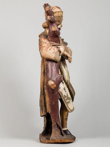 Gefasste Holzskulptur des an einen kahlen Baumstamm gefesselten heiligen Sebastian in vornehmer Gewandung, Seitenansicht von links.