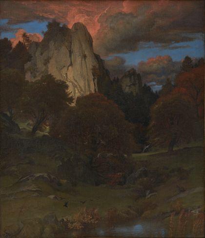 Dunkle Herbstlandschaft. Die Bäume sind bereits rot, im Hintergrund ragt der Scharfenstein in den rot glühenden Abendhimmel.