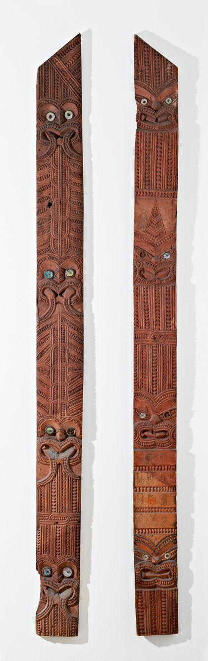 Eingangspfosten in Form eines schmalen, langen Brettes, dessen Schnitzereien Zackenbänder und (Dämonen-)Masken zeigen, deren  Augen durch Perlmuttscheiben hervorgehoben sind.
