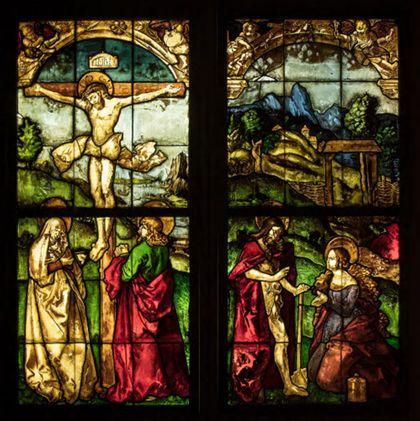 """Kirchenfenster mit Passionsszenen: Vor landschaftlichem Grund ist links die Kreuzigung Christi und rechts die """"Noli me tangere""""-Szene zu sehen."""