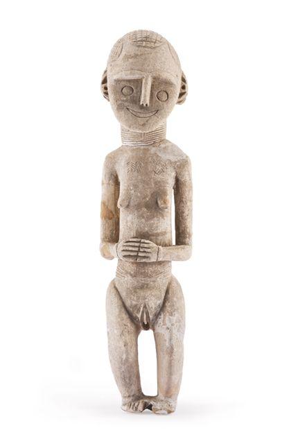 Weibliche Figur aus Kreidestein, mit gebeugte Knien. Frisur, Halsschmuck und Lendengürtel durch Kerbzeichnung dargestellt.
