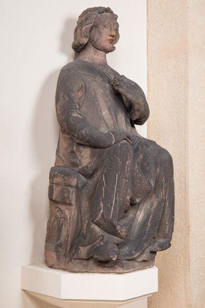 Sitzender Graf mit Stirnreif aus Sandstein, Seitenansicht von links.