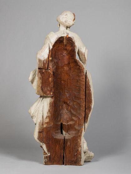 Monochrom hell gefasste Holzskulptur der heiligen Afra, die in lodernden Flammen steht, Rückseite.