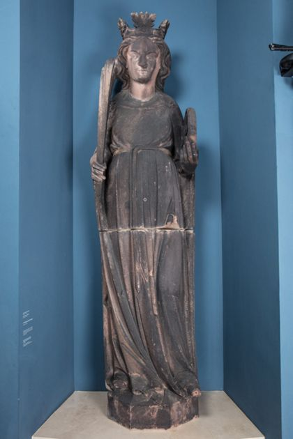 Sandsteinfigur der heiligen Katharina, gekrönt mit Palmzweig und Buch, auf flachem Sockel stehend.