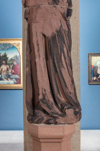 Stark beschädigte, überlebensgroße Sandsteinfigur eines schmalen, in den Proportionen gelängten Propheten mit Kappe, Detail der unteren Partie der Skulptur.