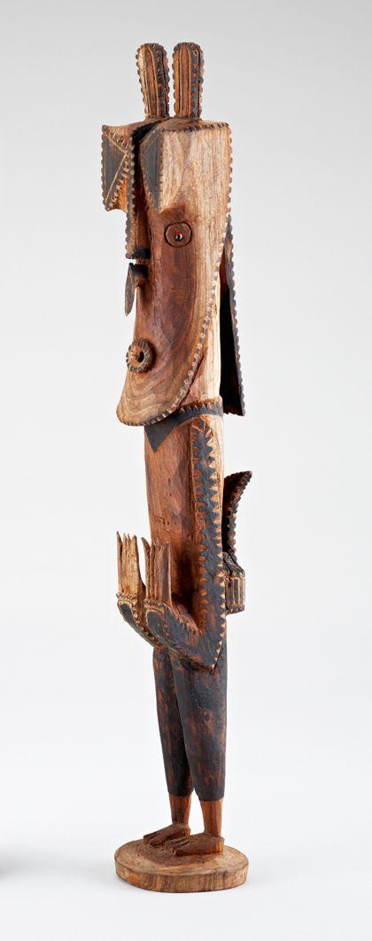 Aus Holz geschnitzte stehende menschliche Figur mit langgezogenem Kopf. Vor der Stirn befinden sich zwei mit der Spitze gegeneinander gestellte Dreiecke. Auf dem Kopf erheben sich zwei senkrechte Ohren.