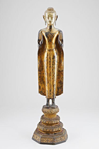 Stark abstrahierter, stehender Buddha aus Bronze auf einem vierfachen Sockel mit reichem Dekor. Gestalt des Buddha ist lackvergoldet auf schwarzem Grund, das Gesicht ohne Vergoldung poliert.