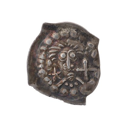 Historische Münze mit Kopf, Sternen und Kreuzen.