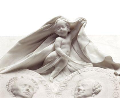 Detail des Putto, der über den Medaillons der verstorbenen Eheleute schwebt und ein Gewand über diese ausbreitet.