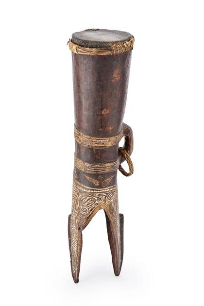 Eine sanduhrförmige Tanz- und Signaltrommel, die mit Schlangenhaut bespannt ist. Unterteil ist gespalten und mit Kerbschnitt-Ornament verziert.