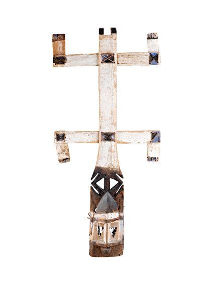 Die Maske mit einem Doppelkreuz-Aufsatz wurde aus leichtem, hellem Holz gefertigt. Sie ist weiß, schwarz und blau bemalt. Am Hinterteil der Maske befindet sich ein Netz.