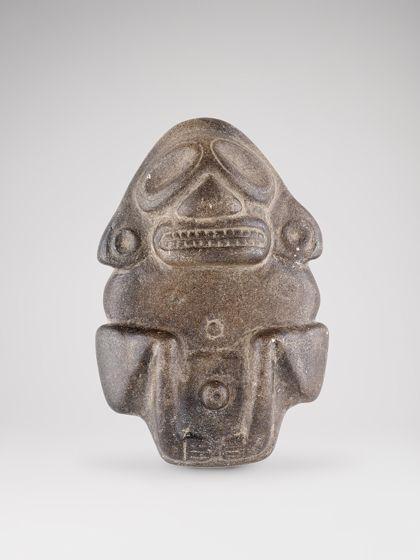 Hockende Figur aus braunem Stein mit stilisierten Gesichtszügen und Körperformen.