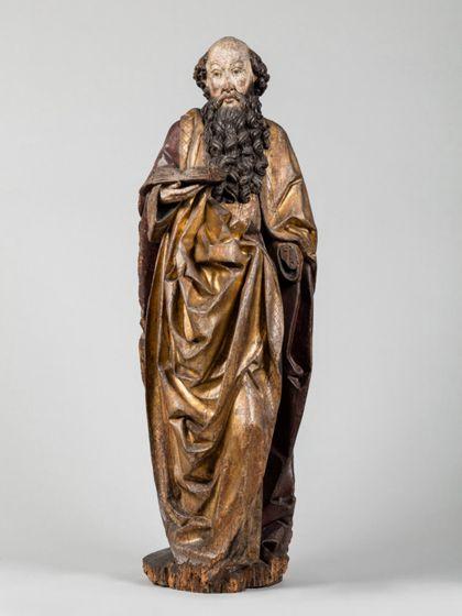 Stehende männliche Holzskuptur mit dunkel gefasstem Vollbart und kahlem Schädel, vermutlich der Apostel Paulus, Seitenansicht von vorne.