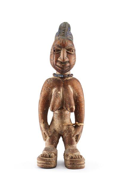 Ibeji Figur aus rotbraunem Holz geschnitzt. Die weibliche Figur steht, die Arme hängen seitlich herab. Stirn und Wangen sind mit Ziernarben versehen. Die Figur trägt ein Halsband aus Glasperlen. An den Vertiefungen der Figur sind Reste roter und blauer Farbe erkennbar.