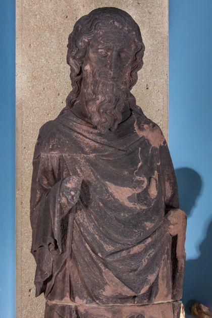 Weit überlebensgroße Sandsteinfigur eines schmalen, in den Proportionen gelängten Propheten ohne Attribute, Detail des Oberkörpers.