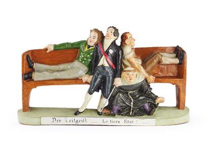 """Die bemalte Tonfigur besteht aus zwei auf einer Bank sitzenden Männern, die einen dritten zu sich drücken. Halb unter der Bank sitzt ein Mönch. Unterhalb der Figuren ist die Aufschrift """"Der Zeitgeist. Le tiers Etat!"""" zu lesen."""