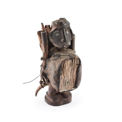 Die männliche Holzfigur trägt einen ovalen Spiegelkasten vor dem Bauch, der Spiegel ist nicht erhalten. Die Seiten des Spiegelkastens sind mit einem Baumharz verschmiert. Das Gesicht der Figur ist breit und flach gestaltet, lediglich die Nase, der Mund und der in die Ohren übergehende Haaransatz sind hervorgehoben. Die Augen sind aus Spiegelglas. Die Figur hat keine Arme. Statt dessen sind rechts und links des Rumpfes zwei Röhrenknochen angebunden. Auf den Rücken der Figur ist ein Bündel getrockneter Blätter gebunden.