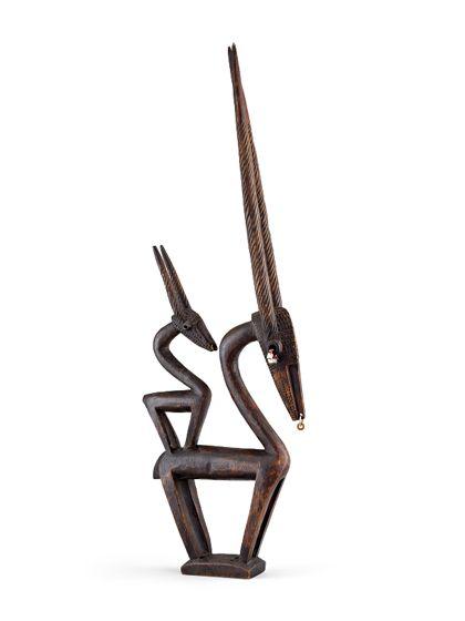 Antilopen-Aufsatzmaske aus Holz geschnitzt. Kleine Anhänger aus Schnecken und Perlen sind angebracht. Die Maske stellt eine weibliche Antilope mit Jungtier dar.
