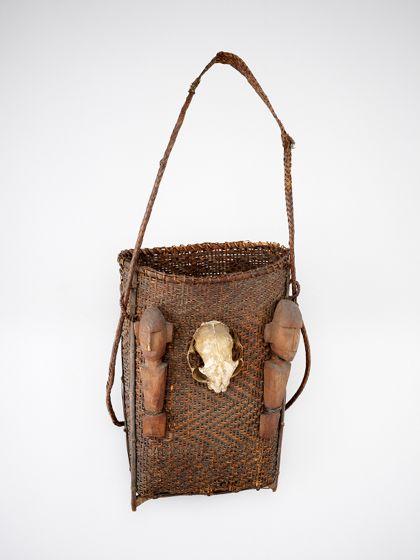 Ein Tragkorb aus geflochtenem, pflanzlichen Material mit Standfüßen und einem Tragband. Der Korb ist mit vier aufgebundenen Holzfiguren und einem Tierschädel verziert.