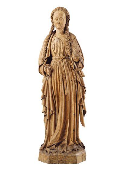 Holzskulptur einer vollrund ausgearbeiteten, stehenden weiblichen Heiligen in langem Gewand mit vier langen Zöpfen. Das Attribut ist verloren.