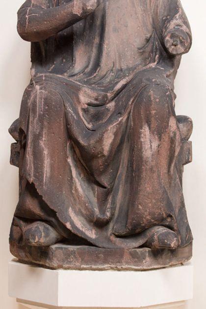 Sandsteinfigur eines sitzenden Grafen mit Blütenkranz, Detail der unteren Partie der Skulptur.