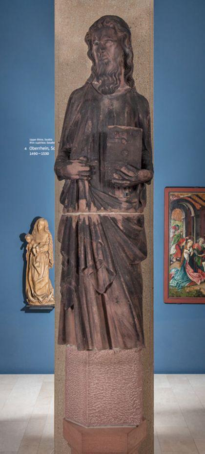 Weit überlebensgroße Sandsteinfigur eines schmalen, in den Proportionen gelängten Propheten mit Buch.