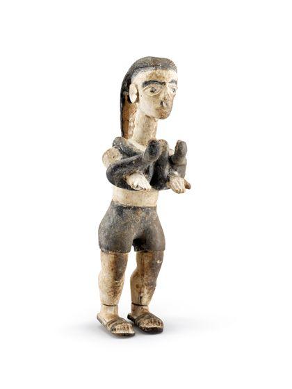 Figur aus Holz, die eine Schlange in den Händen hält.