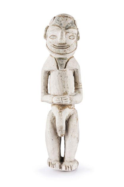 Männliche Figur aus Kreidestein ohne Sockel, deren Knie gebeugt sind. Augen und Mund werden durch schwarze Bemalung angedeutet.