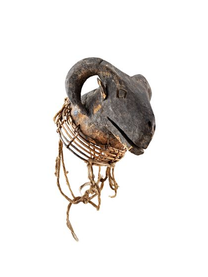 Aufsatz-Maske mit gebogenem Gehörn aus hellem Holz, schwarz gefärbt. Am Unterrand angesetztes Geflechtsstück zum Tragen der Maske auf dem Kopf.
