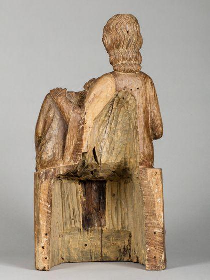 Christus und Johannes sitzen dicht nebeneinander. Johannes hat seinen Kopf an die Brust Jesu gelehnt. Dieser hat eine Hand auf seine Schulter gelegt. Ansicht der ausgehöhlten Rückseite.