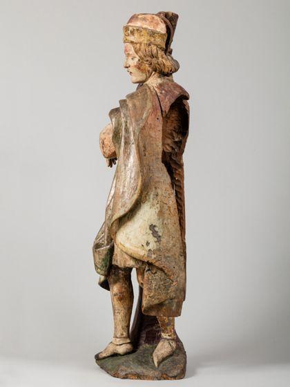 Gefasste Holzskulptur des an einen kahlen Baumstamm gefesselten heiligen Sebastian in vornehmer Gewandung, Seitenansicht von rechts.