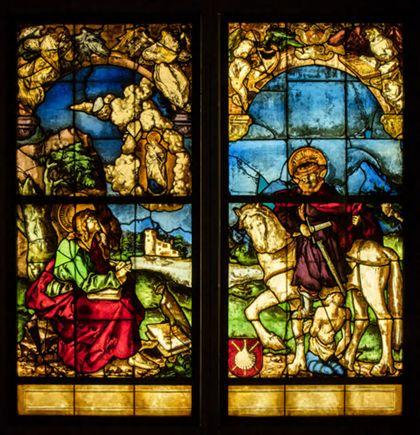 Kirchenfenster mit der Darstellung von Johannes auf Patmos links und dem heiligen Martin, der den Mantel teilt, rechts.
