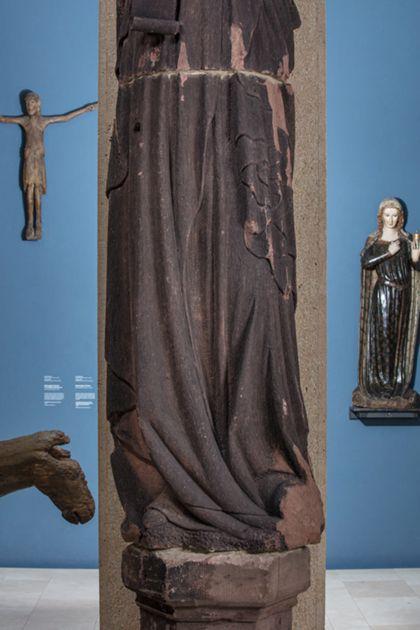 Weit überlebensgroße Sandsteinfigur eines schmalen, in den Proportionen gelängten Propheten mit Kopftuch und Spruchband, Detail der unteren Partie der Skulptur.
