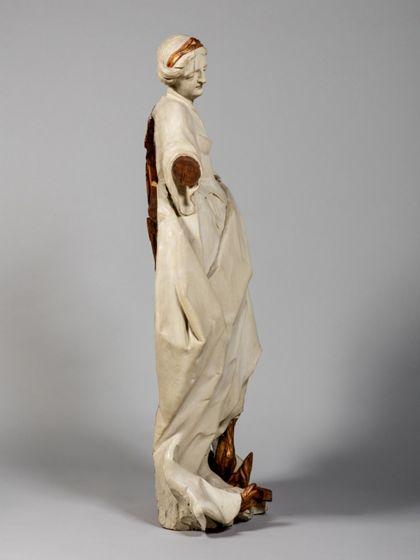 Monochrom hell gefasste Holzskulptur der heiligen Afra, die in lodernden Flammen steht, Seitenansicht von links.