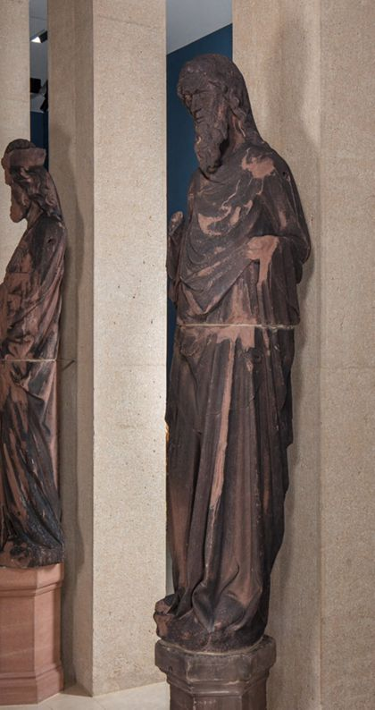 Weit überlebensgroße Sandsteinfigur eines schmalen, in den Proportionen gelängten Propheten ohne Attribute, Seitenansicht von rechts.