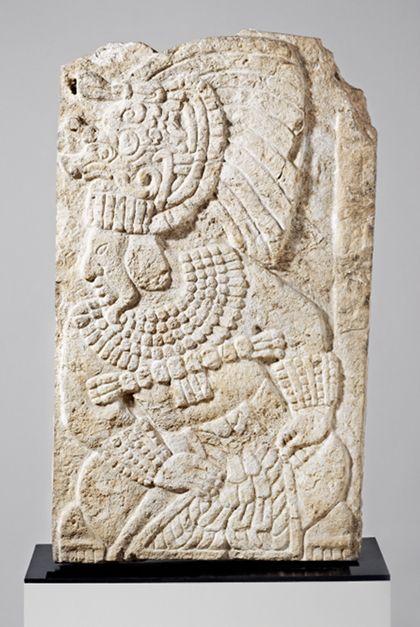 Kalkstein-Relief einer sitzenden Priesterfigur mit reichem Schmuck.