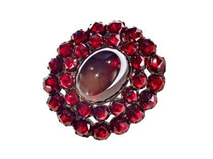 Brosche mit einem größeren dunkelroten Edelstein in der Mitte, umgeben von vielen kleinen granatfarbenen Edelsteinen