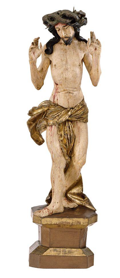 Die gefasste Holzskulptur zeigt Christus als Schmerzensmann auf einem Sockel.