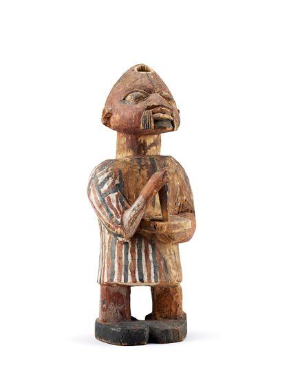 Stehende Figur mit langem Hemd aus Holz geschnitzt und bemalt. Die Figur hält in den Händen ein Messer und ein Brett und ist der Länge nach durchbohrt. Auf dem Kopf steckt in der Bohrung eine Schrotpatrone.