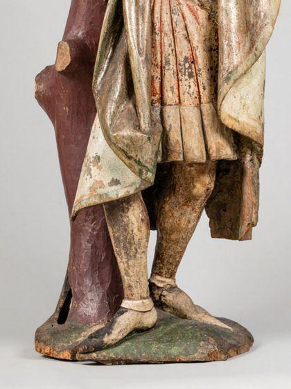 Gefasste Holzskulptur des an einen kahlen Baumstamm gefesselten heiligen Sebastian in vornehmer Gewandung, Detail der unteren Partie der Figur.