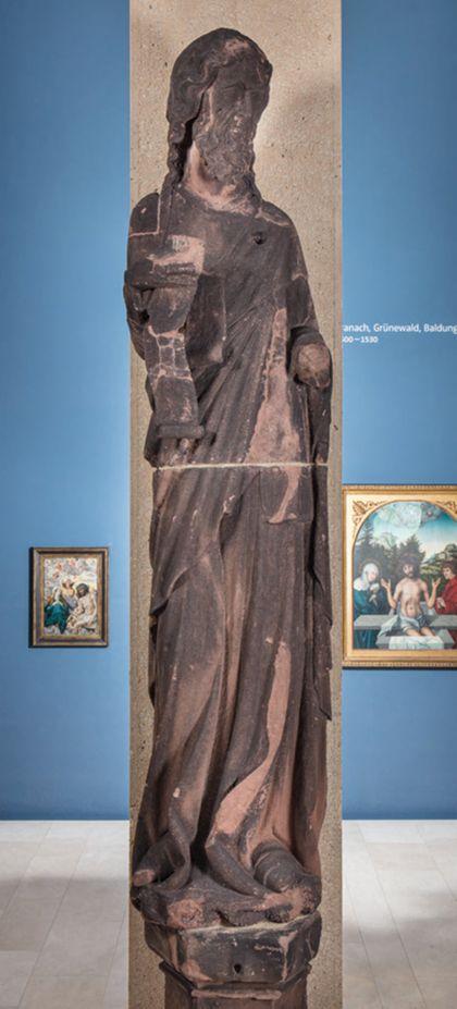 Weit überlebensgroße Sandsteinfigur eines schmalen, in den Proportionen gelängten Propheten mit Spruchband.