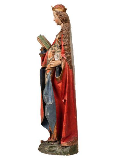 Die gefasste Holzskulptur der heiligen Katharina in langer, vorne geraffter Gewandung hält in der rechten ein Buch, in der Linken ein Schwert, Seitenansicht von rechts.