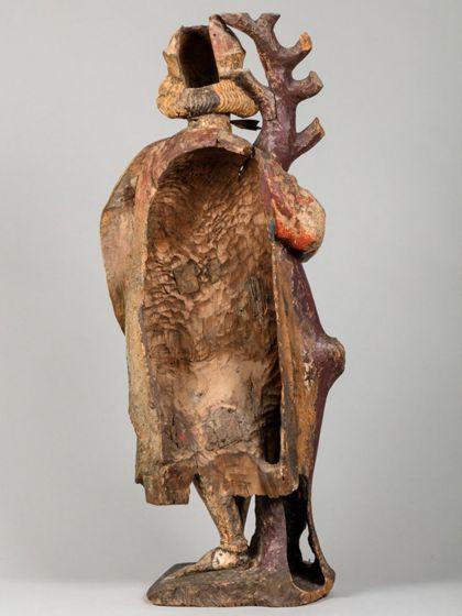 Gefasste Holzskulptur des an einen kahlen Baumstamm gefesselten heiligen Sebastian in vornehmer Gewandung, Ansicht der ausgehöhlten Rückseite.